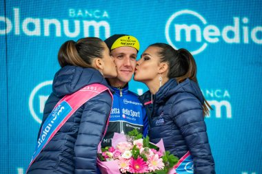 Sappada, Italy May 20, 2018: Simon Yates, Mitchelton-Scott Team, in blue jersey,  celebrates the stage victory on the podium and remains the leader of the Climber classification of Tour Of Italy 2018.