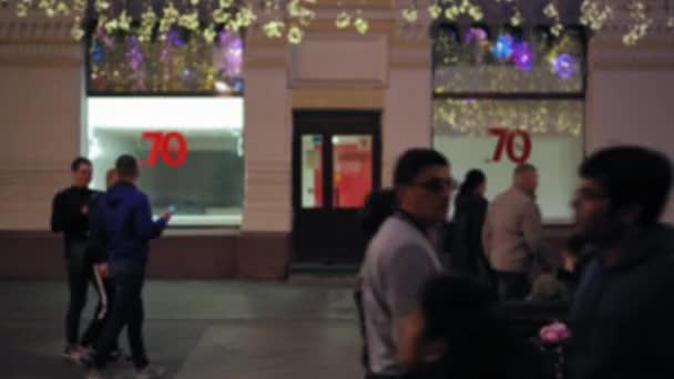 belebte Straße. Fußgänger zu Fuß. Banner, die den Verkauf ankündigen. Weihnachtsbeleuchtung