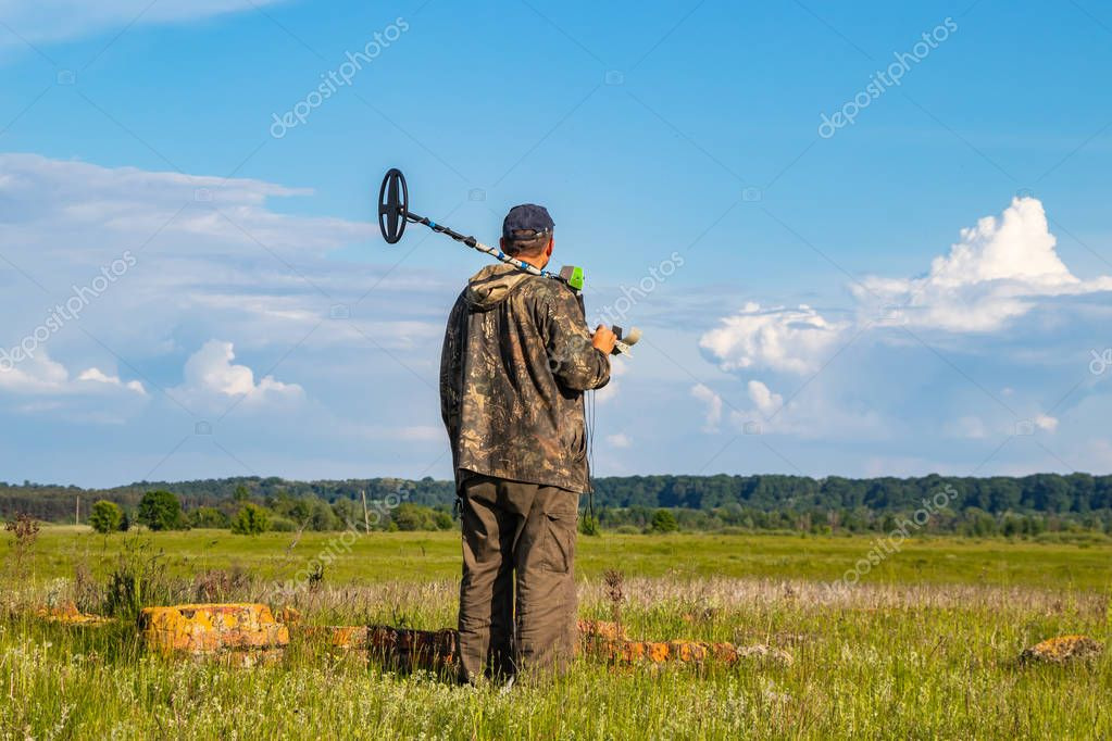 Treasure hunter in the field with a metal detector