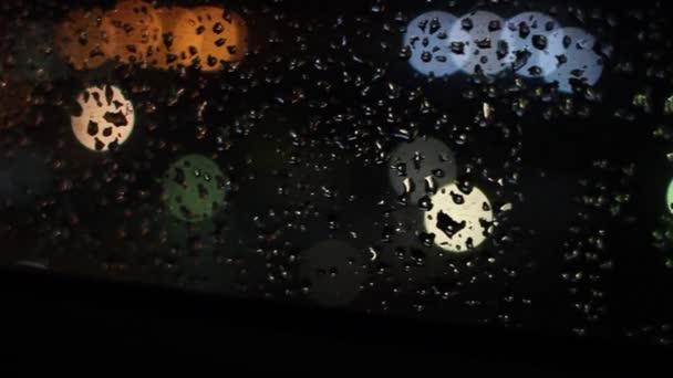 dešťové kapky na skle ve světle nočních světel