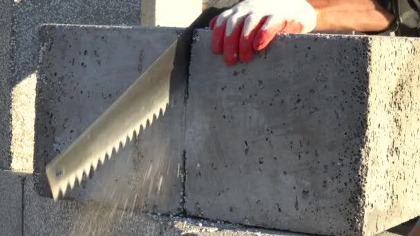 řezání pěnového betonového bloku ruční pilou. koncept výstavby domu