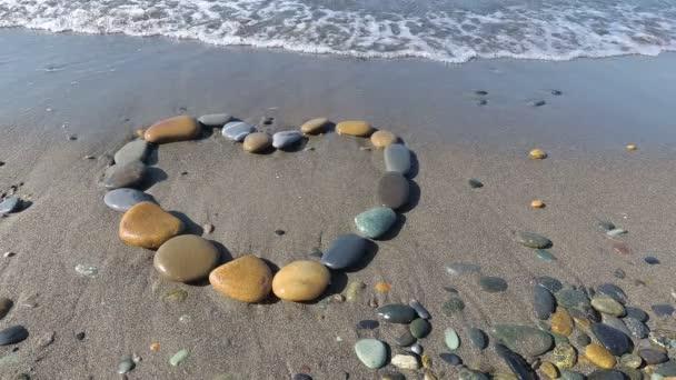 ein Herz aus kleinen Kieselsteinen am Strand