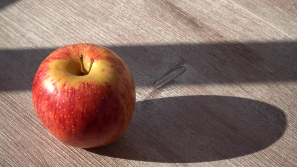 ripe red Apple on a wooden table. sunlight, a game of shadows