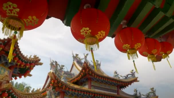 Traditional red lanterns hanging off a buddhist temple structure. Camera movement reveals a traditional buddhist temple architecture.