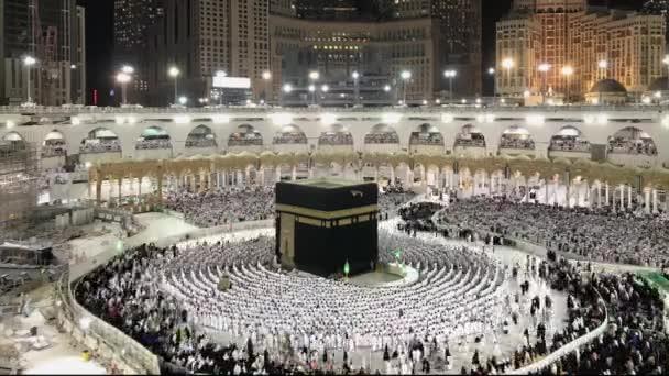 Zeitraffer, in dem muslimische Pilger in weißen ihram-Tüchern vor der Kaaba Schlangen bilden und Abendgebete verrichten.