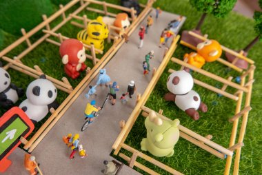 A self constructed miniature toys concept of people at the zoo - school kids, old people sitting on benches, cleaners cleaning the zoo.