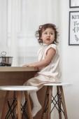 Kis szép lány porszerű ruha mögött ül a szalma a konyhában, és úgy néz ki, közelről, zárt térben