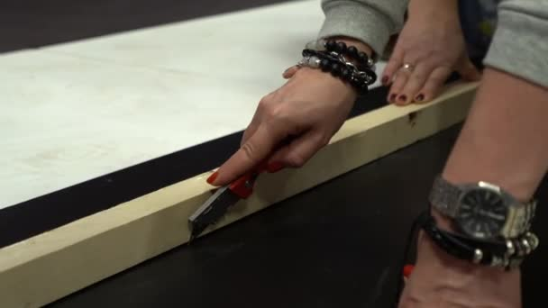 cutting plastic sheet on the floor with blade, knife