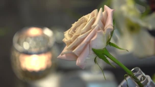 brennende Kerze auf dem Glastisch, Blumengestecke