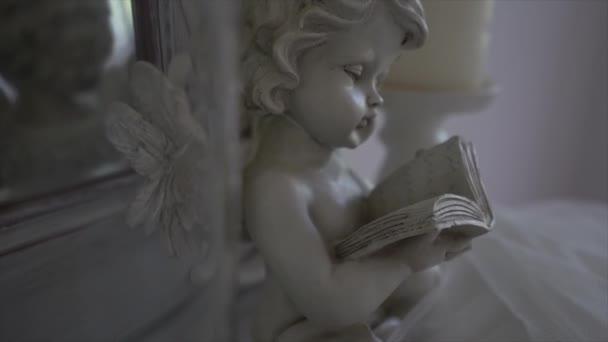 Socha anděla s knihou v ruce