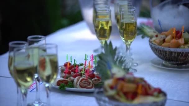 Bufetového stolu s brýlemi šampaňské, ovoce a jednohubky. Žena vezme sklenku šampaňského a svačinu z tabulky