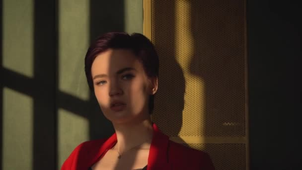 A woman with short purple hair and blue eyes, dressed in black underwear and a red jacket posing for the camera. Shadows fall on the face.Shooting in the Studio