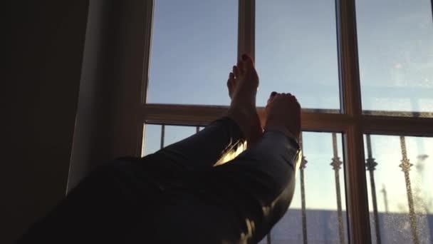 Dámské nohy oblečené v černé kožené kalhoty dotýkala velké okno