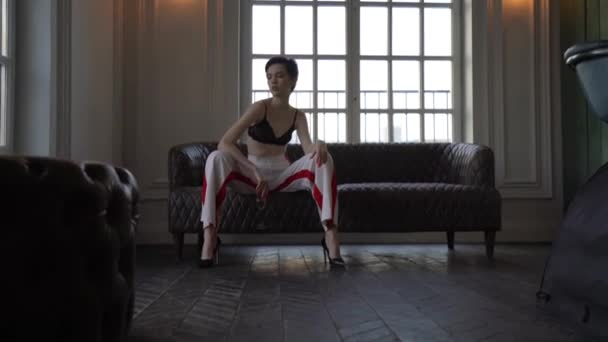 A woman with short hair, dressed in white pants with red stripes and a black bra sitting on the couch legs wide apart in her hand she has a glass of champagne, a woman posing for the camera