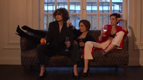 Three women are sitting on the sofa: two of them are sitting and one is lying on it. In the hands of the girls glasses of drinks, one holds a tangerine and throws it, then catches. The rest pose