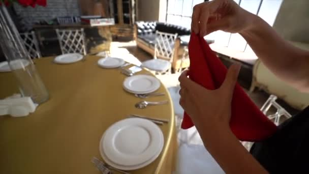 On the table with a Golden tablecloth are white plates, are Cutlery, women's hands are corrected and put on a plate of red cloth napkin