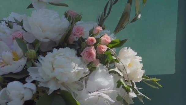Kytice z bílých pivoněk a růžových růží za slunečného letního dne, detail