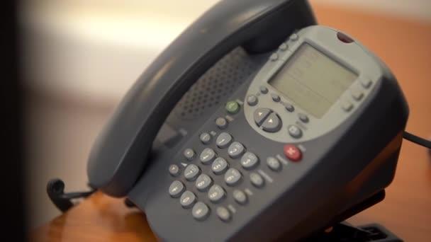Žena položí staré drátový telefon s tlačítky, pak znovu zvedne telefon a vytočí telefonní číslo, pak zavěsí, detail