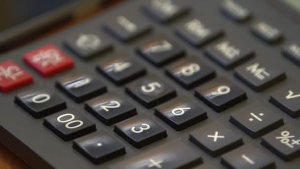 The female hand dials a number, makes calculations on the calculator, close-up only the keys are visible