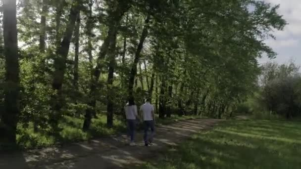 Lovers (man and woman) dressed in blue jeans and white t-shirts , holding hands, hugging, walking on a sandy road, shooting from the back, summer/spring Sunny day