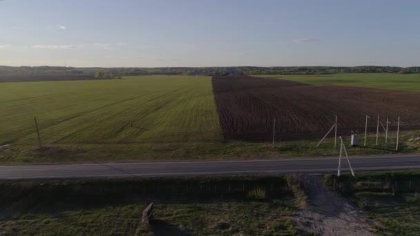 Letecká fotografie: krajina, dálnice, na které auta jdou, pole se zelenou trávou a zatřpylané pole, dva lidé chodí po hřišti v létě/jarní den