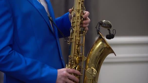 Egy férfi egy fényes kék öltönyt játszik a szaxofon, virtuóz játék, közelről