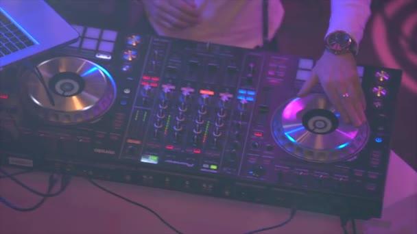 DJ öltözött fehér inget mögött a mixer, mixek zene, fordul a semmiből, felvételi kezek közelről a felső pont. Éjjeli klubparty