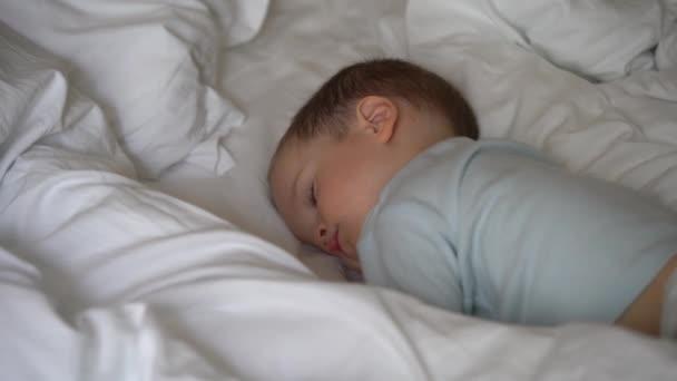 Malé dítě, chlapec ležící v posteli s bílými linény, ranní spánek dítěte, zblízka