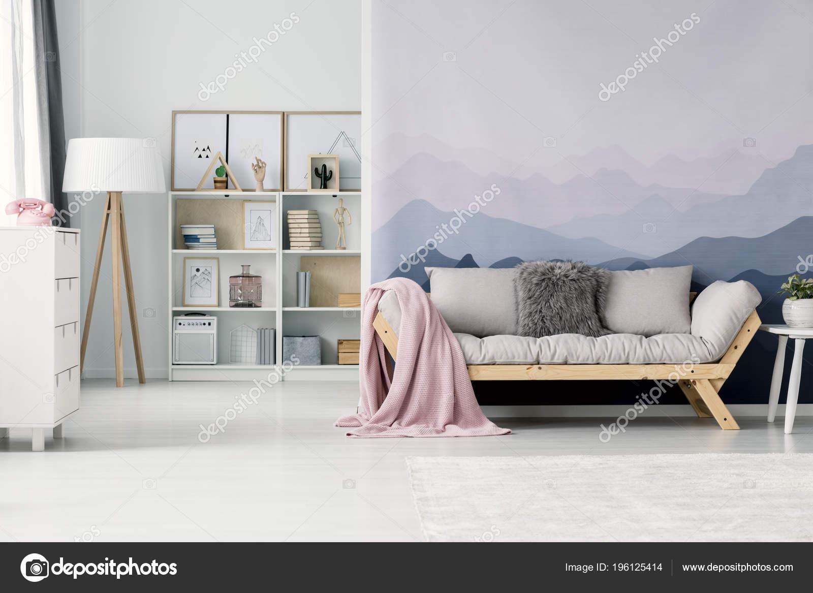 Boekenkast Behang Woonkamer : Gezellige woonkamer interieur met pastel roze deken een beige sofa
