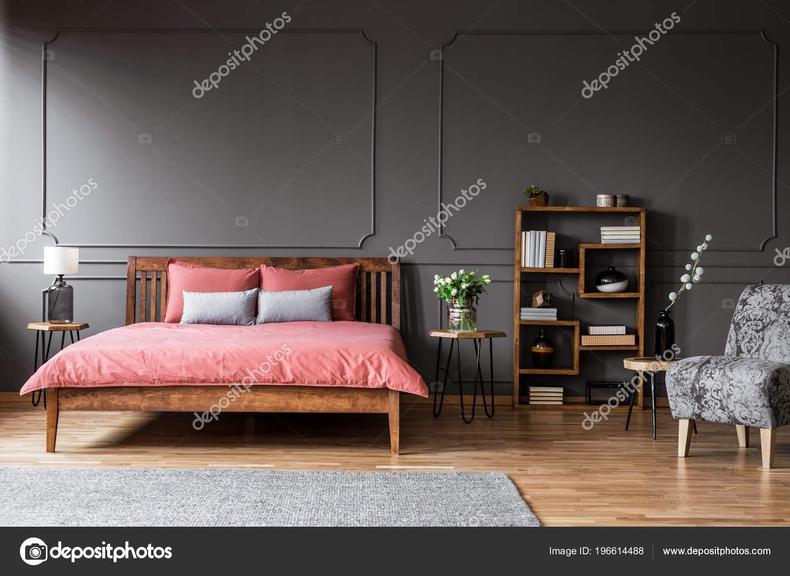 Roze Grijze Slaapkamer : Bloemen houten tafel naast roze bed elegante grijze slaapkamer
