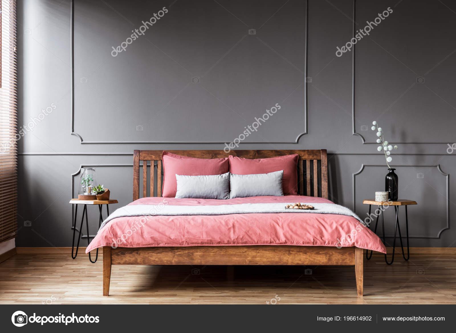 Roze Grijze Slaapkamer : Planten tafel naast een rustieke bed met roze bedlinnen slaapkamer