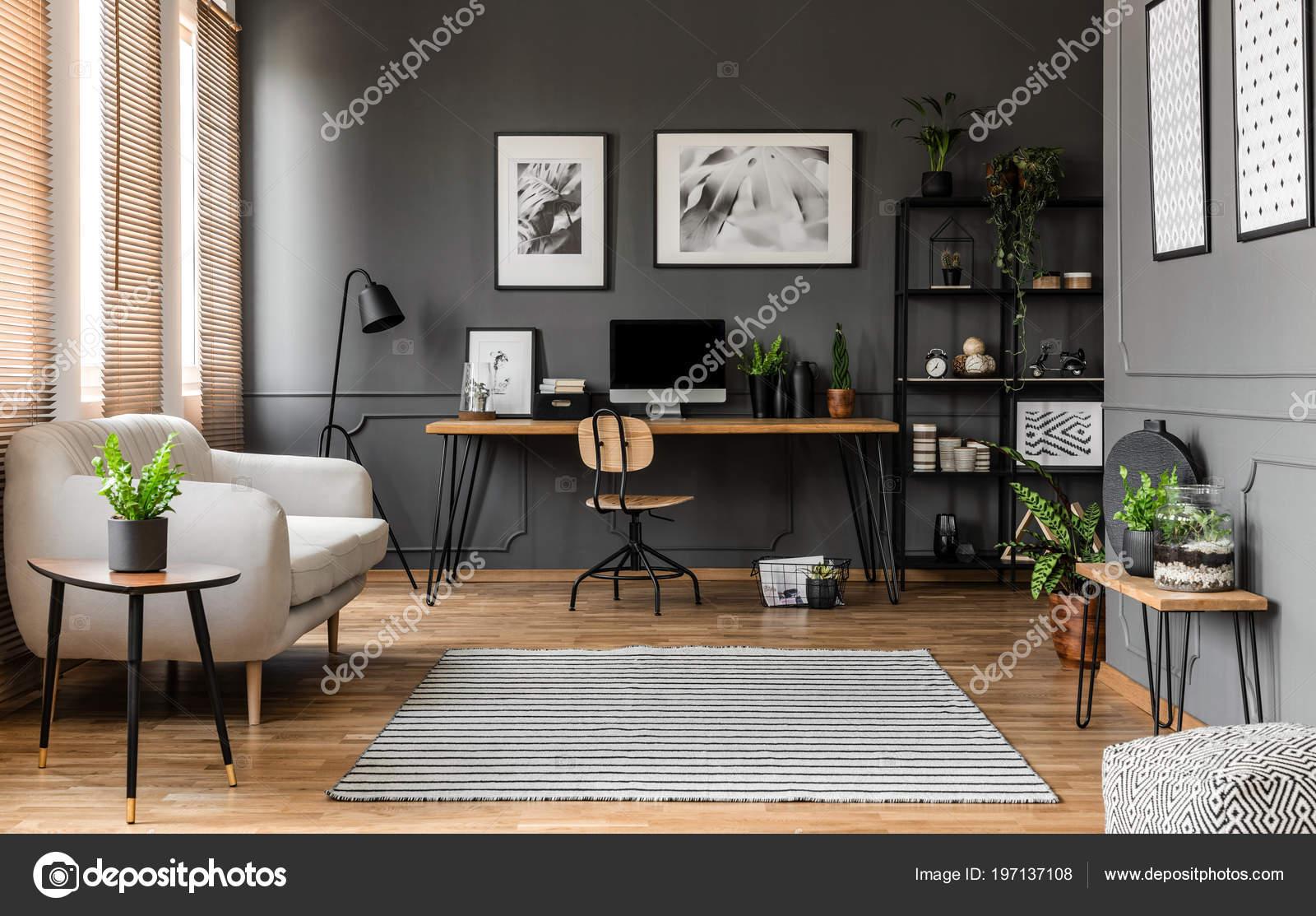 Affiches sur les mur gris dessus bureau bois avec moniteur
