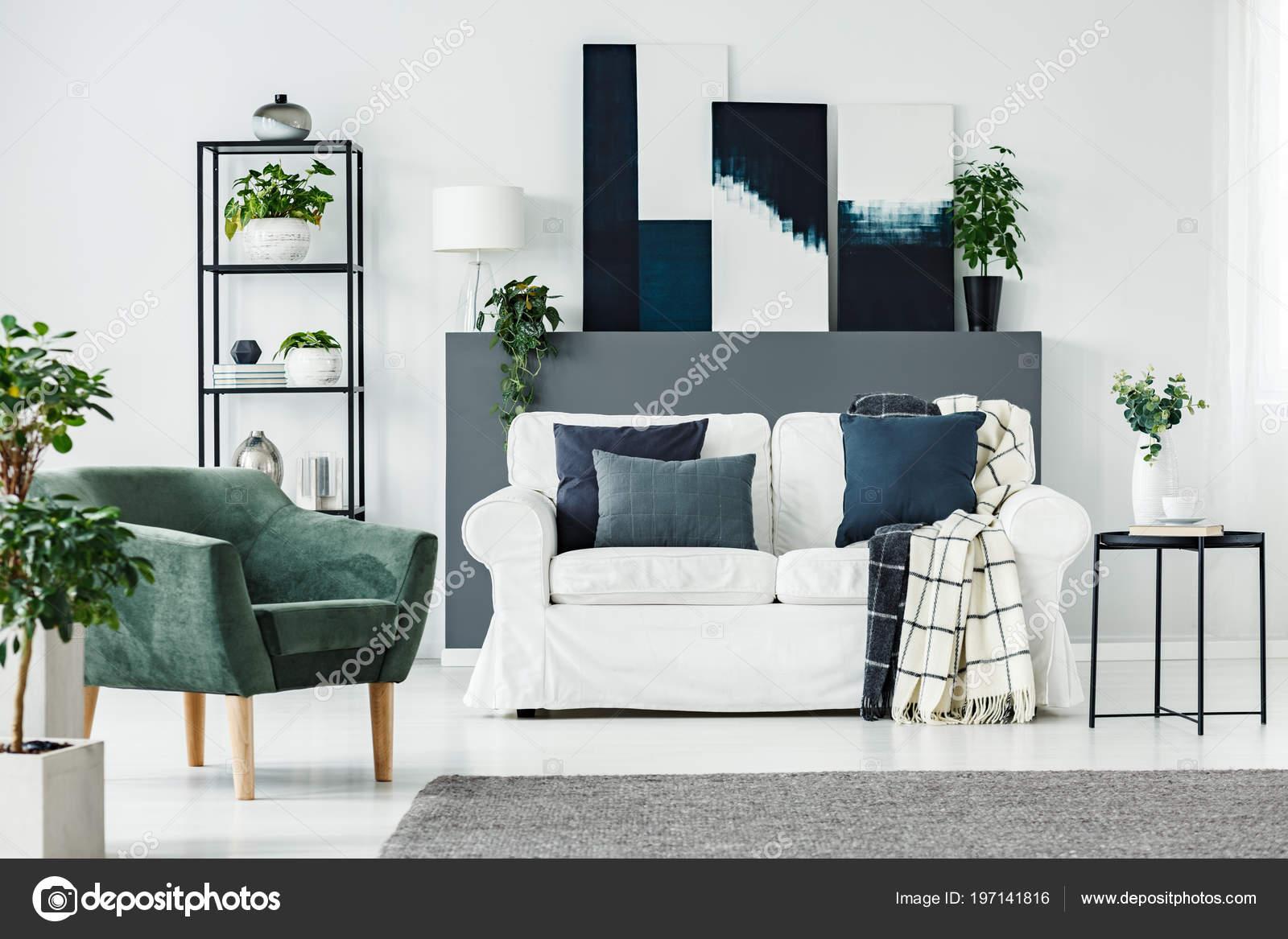 Groene fauteuil witte bank planten grijze muur een moderne