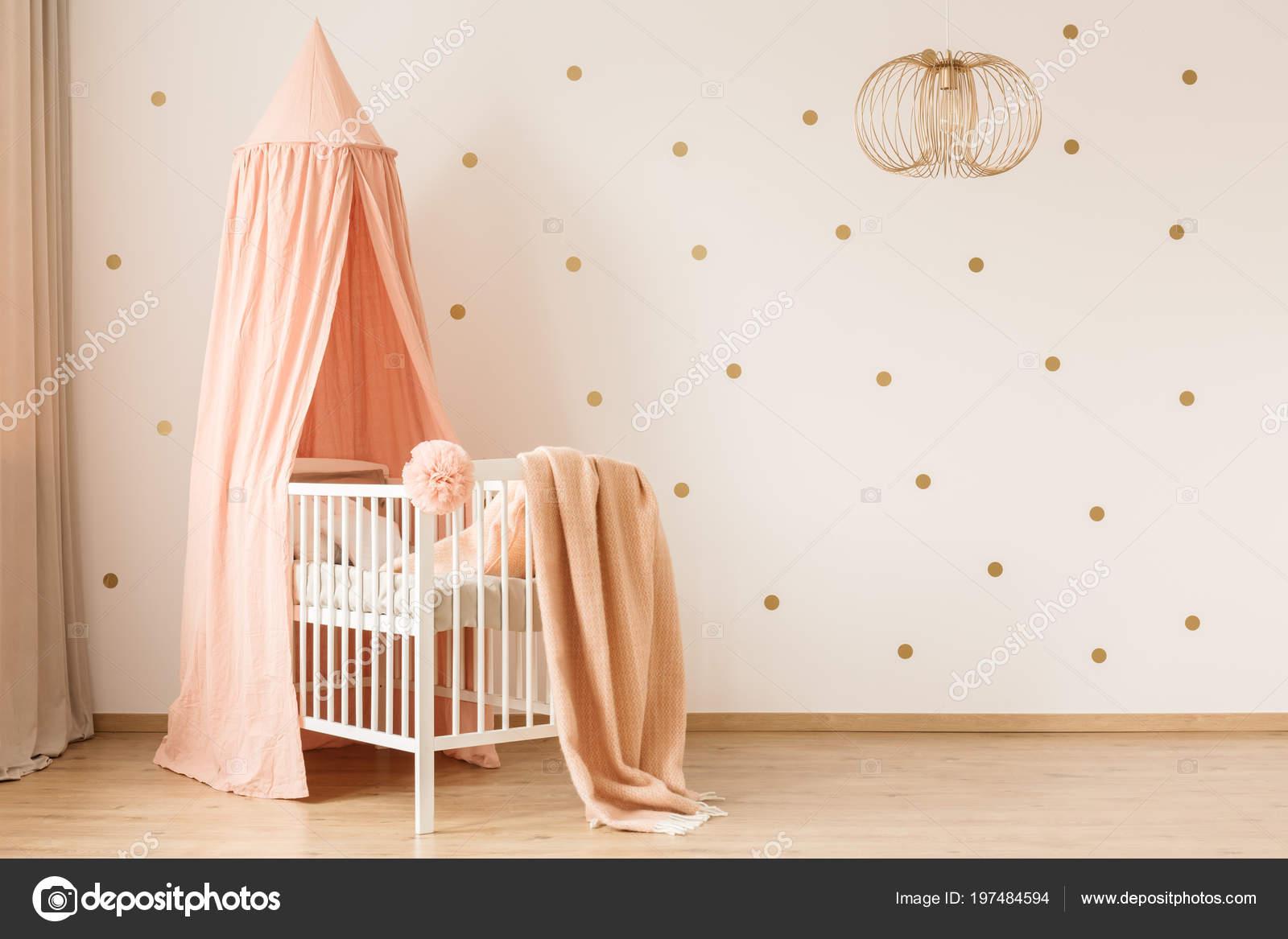 Behang Met Stippen : Gouden lamp pastel baby slaapkamer interieur met canopied wieg tegen