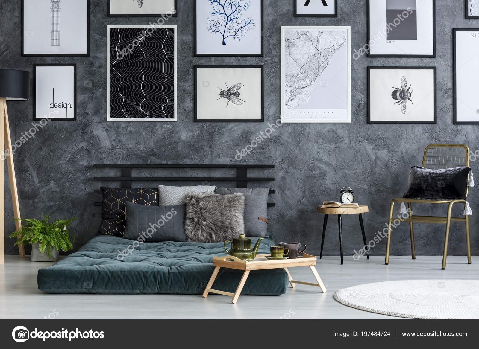 Slaapkamer Groen Grijs : Gouden stoel naast een tabel grijs slaapkamer interieur met posters