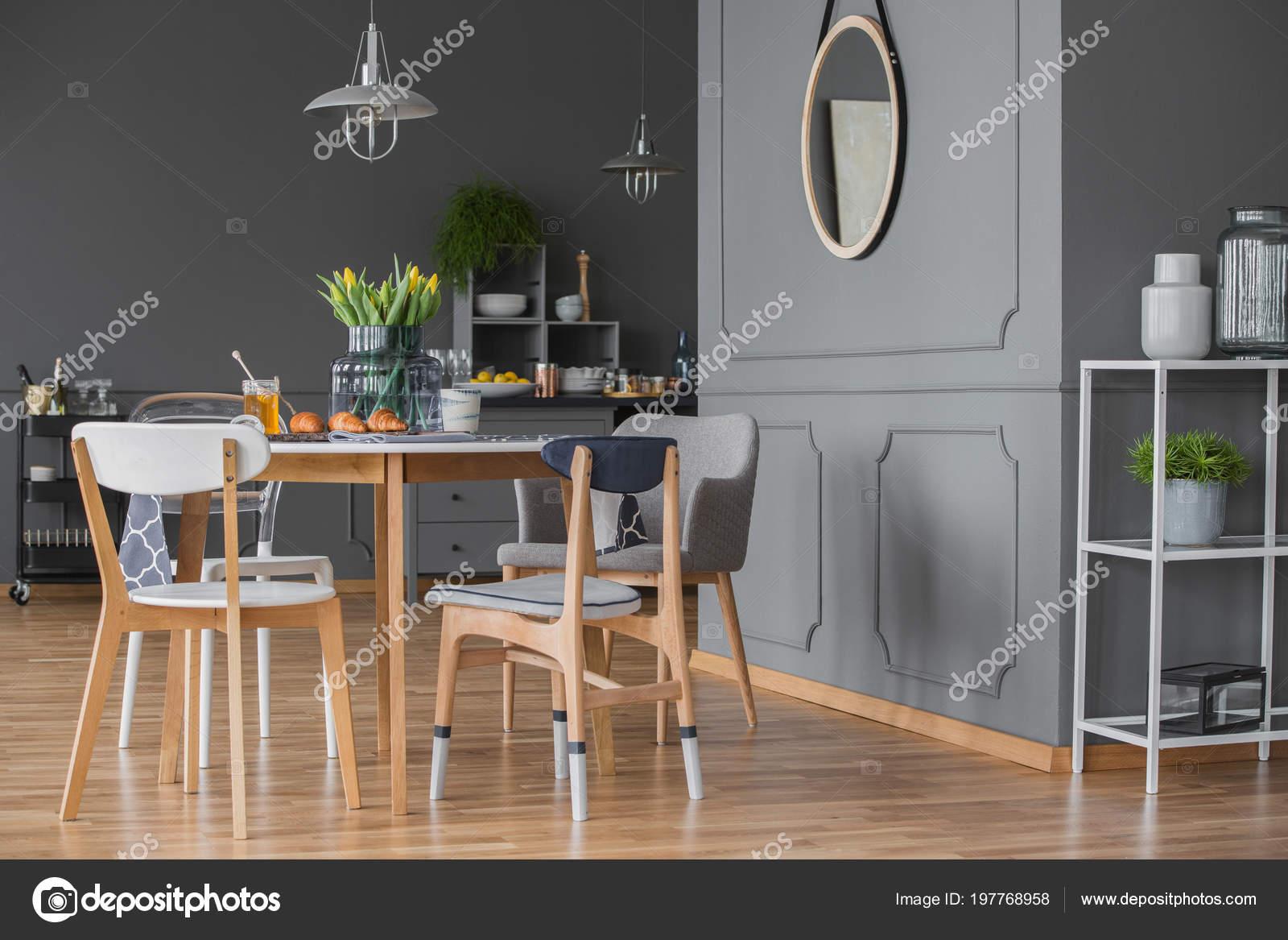 Zijaanzicht van grijze keuken interieur met een eettafel stoelen