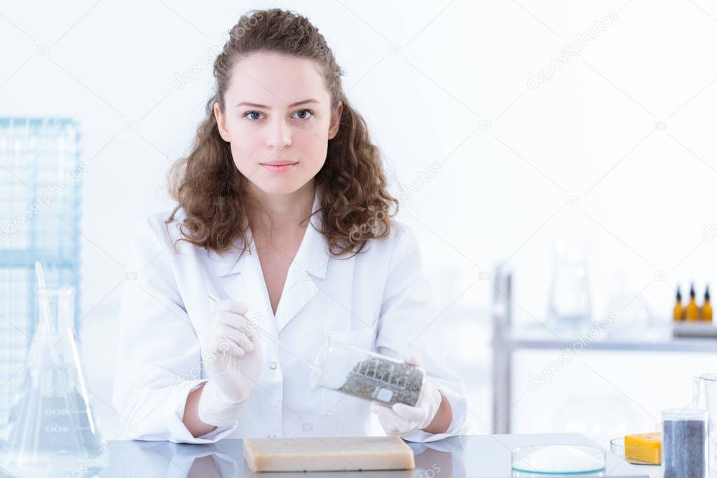 Portrait of a chemist in white uniform getting a sample of a substance from a beaker