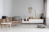 Fotografie gemusterter Hocker auf Teppich neben braunem Sofa im modernen Wohnzimmerinterieur mit Lampe auf dem Tisch. echtes Foto