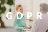 Mladá, lékařka vysvětluje nové Gdpr související politiky svého pacienta. Bílý text na rozmazané Foto
