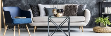 Light grey sofa with decorative pillows standing in dark living room interior with metal table, fresh plant and blue armchair with book