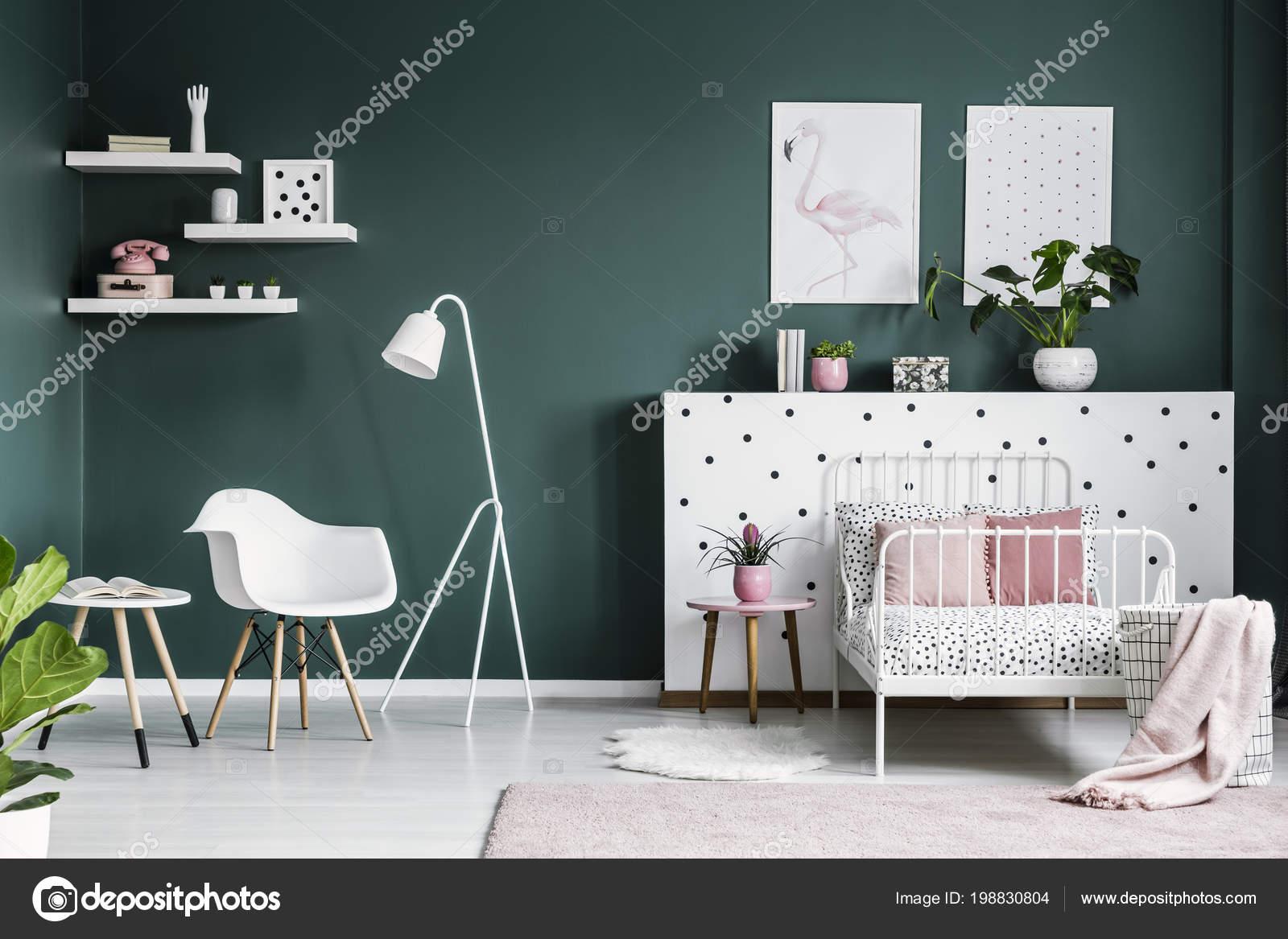 Lampada bianca accanto una poltrona interno camera letto della