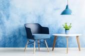 Lámpa fehér asztal mellett egyszerű nappali belső sötétkék fotel a növény fölött