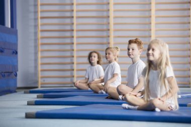 Smiling pupils sitting on blue mats during corrective gymnastics classes