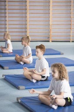 Group of kids sitting in lotus pose during yoga classes at school
