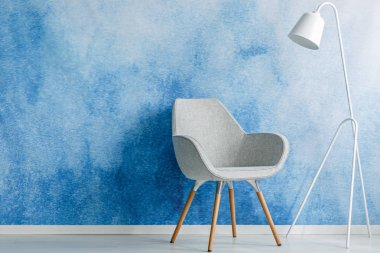 Chair and white lamp set on an empty, blue wall in living room interior. Place your product stock vector