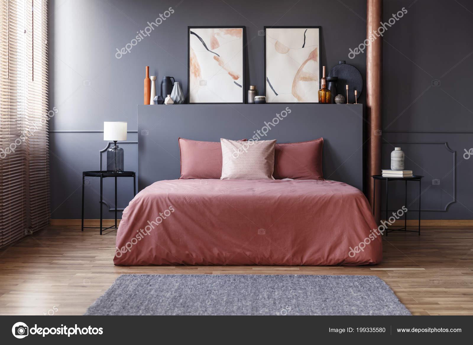 photo reelle d un interieur simple chambre avec sale literie rose sur le lit debout contre le mur gris fonce avec le bati entre deux tables de chevet