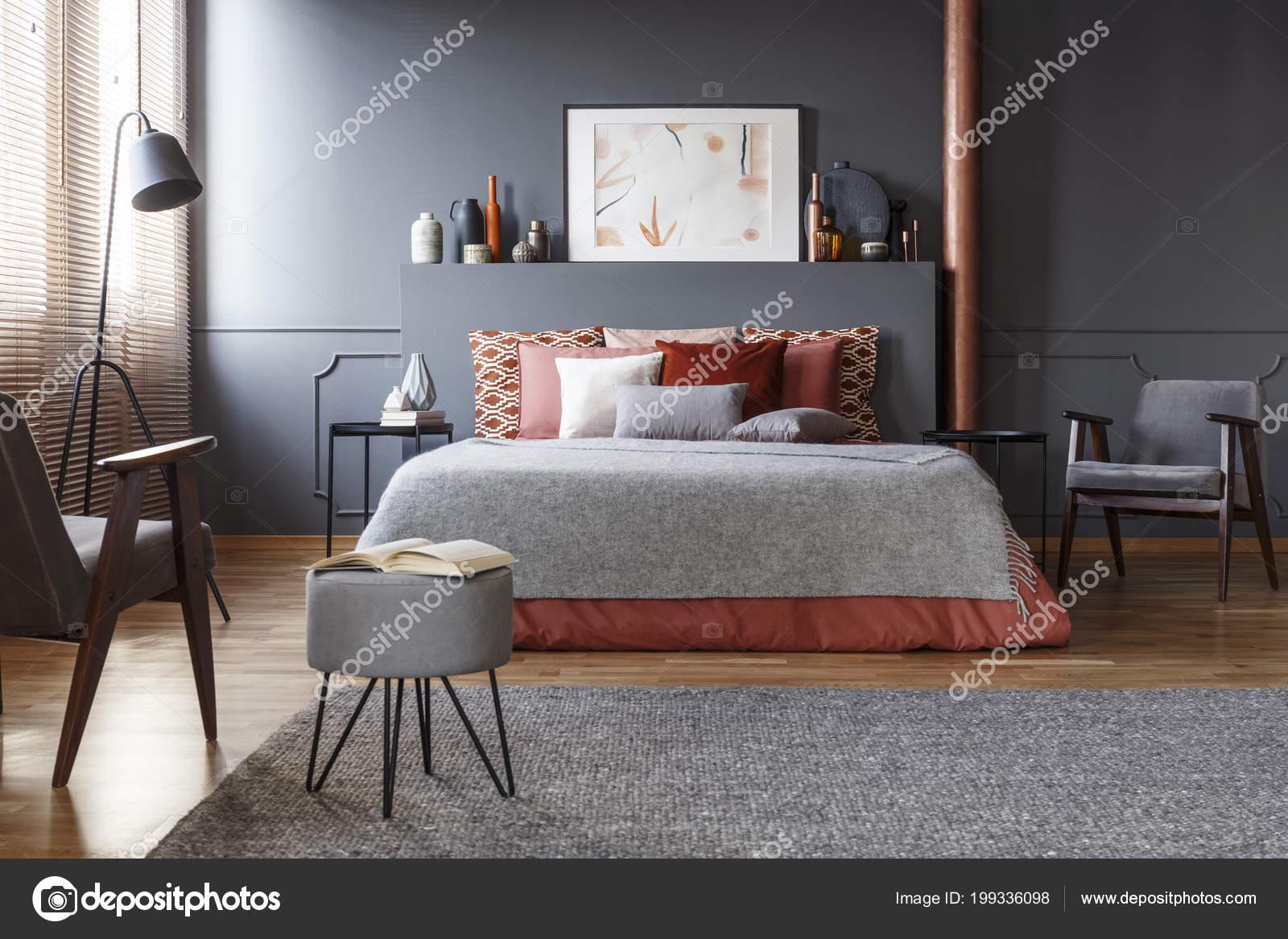 echte foto van gezellige donkere slaapkamer interieur met veel decoratieve stockfoto