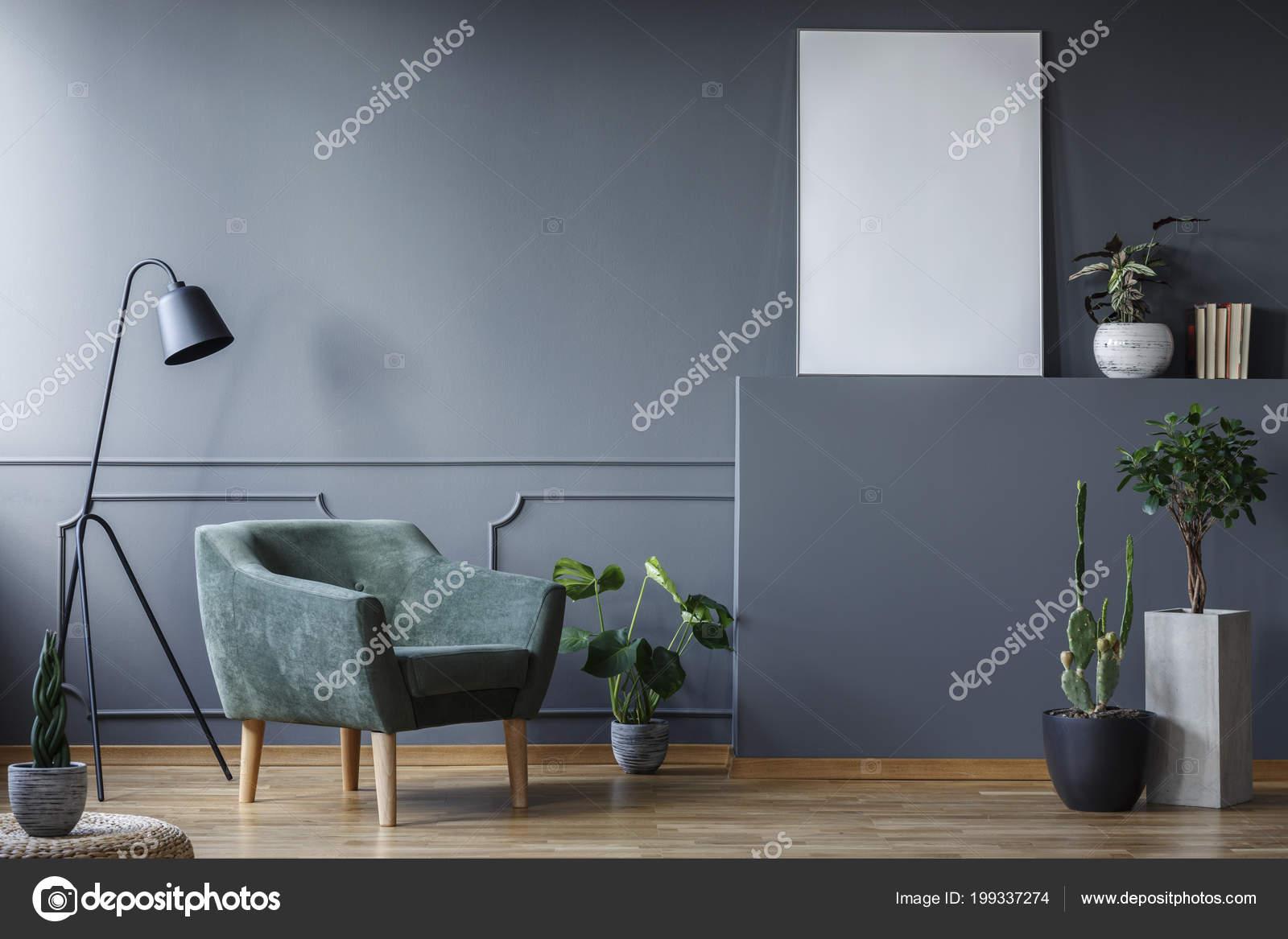 Zwarte lamp naast groene fauteuil woonkamer interieur met planten