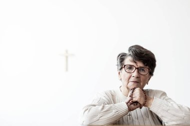 Catholic elderly woman praying to god in a room with copy space