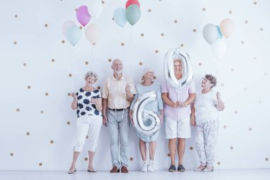 Enthusiastic elderly people with colorful balloons celebrating friend's birthday